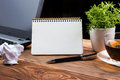 Office table desk with supplies, white blank note pad, cup, pen, pc, crumpled paper, flower on wooden background. Top Royalty Free Stock Photo
