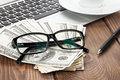 Office table with pc, coffee cup and glasses over money cash Royalty Free Stock Photo