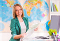 Office travel agency portrait of a young woman chooses a place to using map sitting in Royalty Free Stock Image