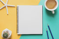 Office workplace minimal concept. Blank notebook with cup of coffee, starfishes, cactus, pencil on yellow and blue background. Royalty Free Stock Photo