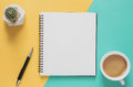 Office workplace minimal concept. Blank notebook with cup of coffee, cactus, pencil on yellow and blue background. Royalty Free Stock Photo