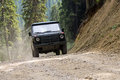 Offroad x vehicle driving on a forest dirt path Stock Photo