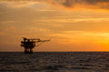 Offshore oil and rig platform in sunset or sunrise time. Construction of production process in the sea. Power energy of the world Royalty Free Stock Photo