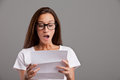 Oh my gosh what i read is amazing brunette young woman realizes that something happened reading a white letter or document Royalty Free Stock Image