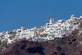 Oia santorini village with the whitewashed typical houses at the top of a steep hill with two windmills greek island of Stock Photography