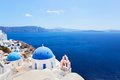 Oia town on santorini island greece caldera on aegean sea traditional and famous houses and churches with blue domes over the Royalty Free Stock Images