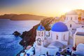 Oia town on Santorini island, Greece at sunset. Rocks on Aegean sea.
