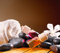 Oil containers stones and towel square composition balls essences for body care with black sheets on wooden base brown gradient Stock Photos