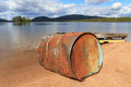 Oil drum at lake rusty old of a raft in a Stock Photos