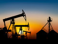 Oil field at sunset near the storage tank Stock Photography