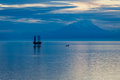 Oil and gas platform in the cook inlet reflecting on water with snow capped mountains background Stock Photos