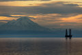 Oil and gas platform in cook inlet with snowcapped mountain snow covered background at sunset Royalty Free Stock Photo