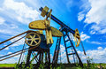 Oil and gas pump operating machinery profiled on blue sky Stock Photography