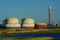 Oil gas storage tanks and chimney close to a lake Stock Photo