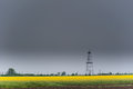 Oil and gas well rig outlined rural canola field on on an overcast day Royalty Free Stock Image