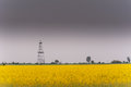Oil and gas well rig outlined rural canola field on on an overcast day Stock Photography
