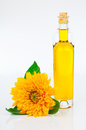 Oil in glass bottle and sunflowers