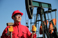 Oil Industry Worker Holding Sledgehammer Next to Pump Jack. Royalty Free Stock Images