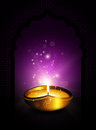 Oil lamp with diwali diya greetings dark background violet Stock Photos