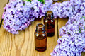 Oil with lilacs on board in a bottle lilac flowers the background of wooden boards Royalty Free Stock Images