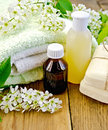 Oil with lotion and bird cherry on board bottles soap flowers a towel the background of wooden boards Stock Photo