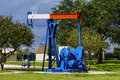 Oil nodding donkey pumpjack a red white and blue used for taking from the ground Stock Image