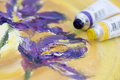 Oil paint tubes purple and yellow are on a corner of canvas with flower painting Stock Image
