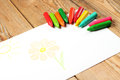 Oil pastel crayons lying on a paper with painted flower and sun children s drawing selective focus copy space background Royalty Free Stock Images