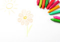 Oil pastel crayons lying on a paper with painted flower and sun children s drawing selective focus copy space background Royalty Free Stock Image