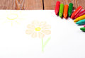 Oil pastel crayons lying on a paper with painted flower and sun children s drawing selective focus copy space background Stock Photo