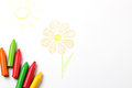 Oil pastel crayons lying on a paper with painted flower and sun children s drawing selective focus copy space background top view Stock Photography