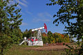 Oil pump on a background of autumn forest and blue sky Royalty Free Stock Image