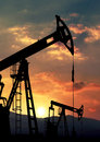 Oil pump jack against sunset Royalty Free Stock Images