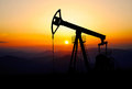 Oil pump jack bringing energy for world in a beautiful sunset Stock Photos