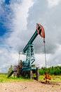 Oil pump jack in the field in Russia under cloudy skies Royalty Free Stock Photo