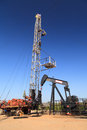 Oil Pump Jack (Sucker Rod Beam) and Workover Rig Royalty Free Stock Photo