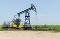 Oil pump well machine in field on clear sunny day horizontal shot Royalty Free Stock Photography