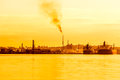 Oil refinery at sunset polluting the air near sea with tanker ships nearby Stock Image