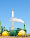 Oil refinery tower belching smoke or steam into the atmosphere Royalty Free Stock Photography
