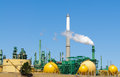 Oil refinery tower belching smoke or steam into the atmosphere Stock Photography