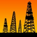 Oil rig silhouettes and orange sky Royalty Free Stock Photo
