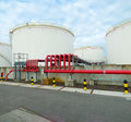Oil storage large tanks for and petrol in the amsterdam harbor area the red pipelines are for water supply in case of an fire Royalty Free Stock Photos