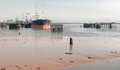 Oil tanker at port during low tide an ship docked a wharf and amongst old piers and misty skies Stock Photography