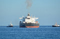 Oil tanker towed by tugs after unloading of crude Stock Images