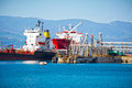 Oil tankers bringing their cargo in a tank storage facility Stock Photography