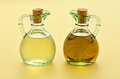 Oil and vinegar olive rice wine in pretty glass jugs on a warm yellow background Royalty Free Stock Photo