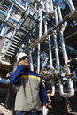 Oil worker talking in phone inside refinery and gas with detail background Stock Photo