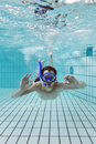 Ok hand signal underwater young male diver giving an wearing a snorkle and diving glasses in an indoor swimming pool Stock Photos