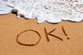 Ok message written sand wave approaching Stock Photo