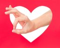 Okay gesture woman hand shows against red heart concept Stock Images
